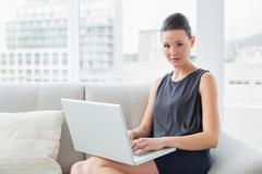Beautiful well dressed young woman using laptop on sofa - stock photo