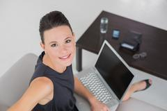 Beautiful well dressed woman with laptop on sofa Stock Photos