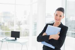 Elegant businesswoman leaning on glass wall with folder Stock Photos
