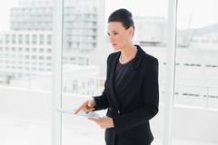 Elegant woman holding a document in office - stock photo