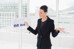 Businesswoman with graphs standing in bright office Stock Photos