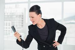 Stock Photo of Elegant businesswoman shouting into the phone