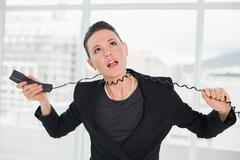 Frustrated elegant businesswoman with telephone cable around her neck - stock photo