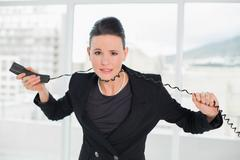 Frustrated elegant businesswoman with telephone cable around her neck Stock Photos
