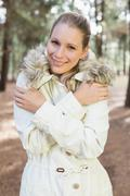 Cute woman shivering while having a walk in a forest Stock Photos