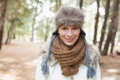 Stock Photo of Woman wearing fur hat with woolen scarf and jacket in woods