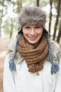 Beautiful woman wearing fur hat with woolen scarf and jacket in woods Stock Photos