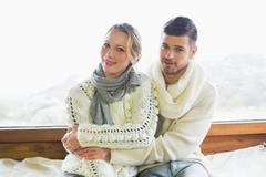 Stock Photo of Couple in winter clothing sitting against window