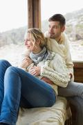 Couple in winter wear looking out through cabin window - stock photo