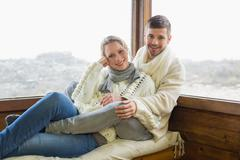 Couple in winter clothing sitting against cabin window - stock photo