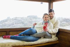 Couple in winter wear with coffee cups against cabin window - stock photo