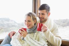 Stock Photo of Couple in winter wear drinking coffee against window