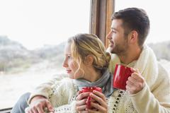 Stock Photo of Couple in winter wear with cups looking out through window