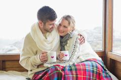 Stock Photo of Loving couple in winter wear with cups against window