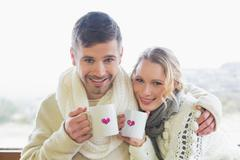 Stock Photo of Loving couple in winter clothing with coffee cups against window