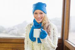 Stock Photo of Woman with coffee cup in warm clothing against window
