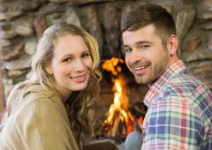 Smiling young couple in front of lit fireplace Stock Photos
