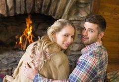 Romantic young couple in front of lit fireplace - stock photo