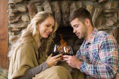 Couple toasting wineglasses in front of lit fireplace Stock Photos