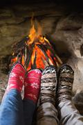 Romantic couple's legs in socks in front of fireplace - stock photo