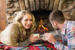 Couple with tea cups in front of lit fireplace - stock photo