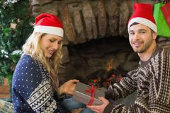 Man gifting woman in front of lit fireplace during Christmas Stock Photos