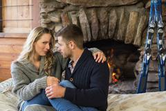 Young couple in front of lit fireplace - stock photo