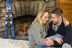 Romantic couple with arms around in front of lit fireplace - stock photo