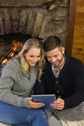 Lovely couple using tablet PC in front of lit fireplace - stock photo