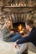 Stock Photo of Couple with wineglasses in front of lit fireplace