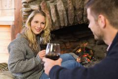 Couple with wineglasses in front of lit fireplace - stock photo