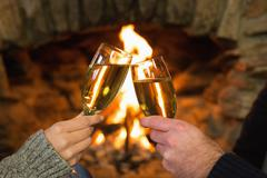 Hands toasting champagne flutes in front of fireplace Stock Photos