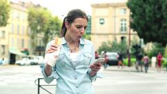 Woman using smartphone and eating baguette by the city street HD Stock Footage