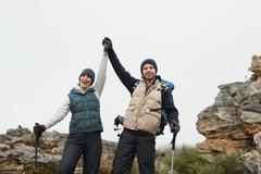 Couple on rocky landscape with hands raised against sky Stock Photos