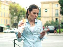 Woman using smartphone and eating baguette by the city street NTSC Stock Footage