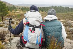 Couple with backpack and trekking pole on a hike - stock photo