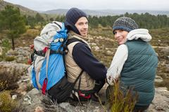 Portrait of a couple with backpack relaxing while on a hike - stock photo