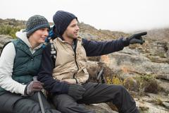 Couple on rock with trekking poles while on a hike Stock Photos