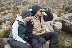 Stock Photo of Couple sitting on rock with binoculars while on a hike