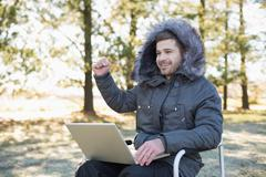 Cheerful man in fur hood jacket using laptop in the forest - stock photo