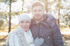 Stock Photo of Smiling couple in winter clothing in the woods