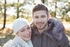 Smiling couple in winter clothing in the woods - stock photo