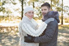 Loving young couple in winter clothing in the woods - stock photo