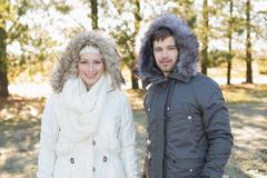 Smiling couple in fur hood jackets in the woods - stock photo