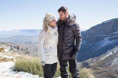 Couple in fur hood jackets against mountain range - stock photo