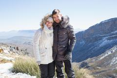 Smiling couple in fur hood jackets against mountain range - stock photo