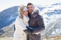 Loving couple in fur hood jackets against snowed mountain range - stock photo