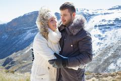 Loving couple in jackets against snowed mountain range - stock photo
