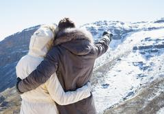 Couple in fur hood jackets looking at snowed mountain range - stock photo
