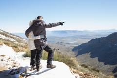 Couple in jackets looking at mountain range - stock photo